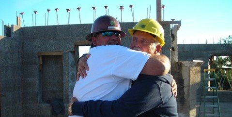 Green Building America Lead Foreman Mike Bourgeois (left) receives a warm embrace from Tea Fire survivor Carmine Santandrea (right)