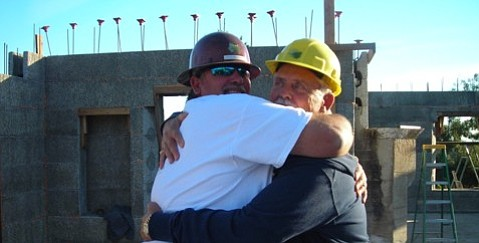 Green Building America Lead Foreman Mike Bourgeois (left) receives a warm embrace from Tea Fire survivor Carmine Santandrea (right)