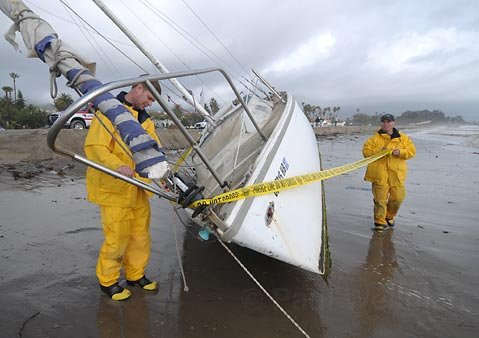 Harbor Patrol Officers Ryan Kelly (left) and Billy Petrini put police tape around an unidentified beached boat on East Beach Jan. 18, 2010