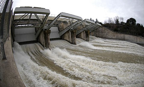 <strong>Piscine needs:</strong>  It remains unclear how much water from Bradbury Dam at Lake Cachuma —shown spilling on January 10, 2005—will have to be set aside to create spawning habitat for the federally endangered steelhead trout.