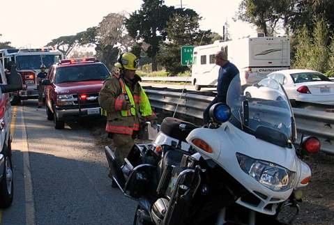 A Montecito Fire battalion chief leans handcuffed against the highway guardrail.