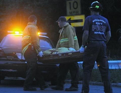 Authorities transport the body of John River after it was sighted by a passing motorist.