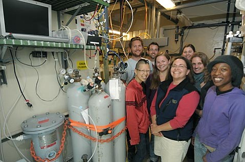 <strong>SMILING SCIENTISTS, SCARY FINDINGS: </strong> Dr. Gretchen Hofmann, front and center in the black vest, and her team of researchers at UCSB are part of a fast-growing international science community scrambling to better understand the impacts of ocean acidification – a phenomenon that has the potential to crash fisheries, rock ecosystems, and change ocean life as we know it. On the left is a CO2 machine essentially invented by Hofmann and crew in order to make their research possible. It allows them to mix exact levels of CO2 with Pacific Ocean water piped in from offshore of Campus Point. The goal is to create future ocean situations and see which organisms survive, thrive, or die with increased acidity.