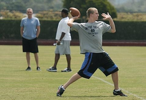 Nate Montana throws a pass while father Joe looks on
