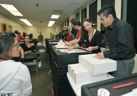 Augie Aguilar, far right, gets initial handling instructions from Melinda Greene as the first boxes of ballots come in to the Elections office for tallying, June 8, 2010.