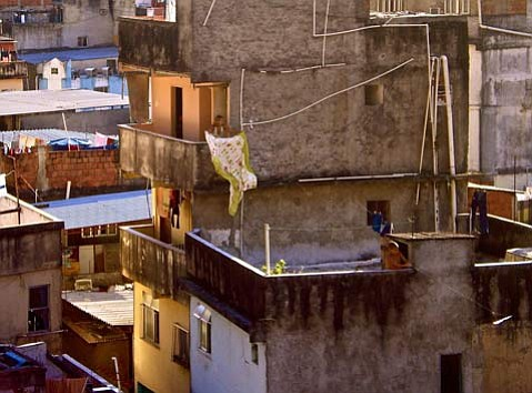A boy wills the wind to take his kite higher from his rooftop in Rocinha.
