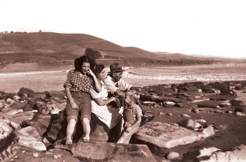 """<strong>BEACH DAYS:</strong>After patriarch Don Bruno Orella died in 1901, his children inherited adjacent ranches in Refugio, Venadito, and Corral canyons. His son Victor received Refugio """"beach, some land to the west, a small piece to the east, and a short distance up Refugio Canyon,"""" but soon sold the property to the Rutherfords, whose family immigrated to the area from Scotland. The author's family was close with the Rutherfords and visited the beach regularly, as it was just below their ranch. Pictured are (from left) the author; her mother, Louise """"Honey"""" MacIntyre Erro; her father, Martin Erro; and her sister Zena's son, Martin, on shoreline rocks of Refugio Beach. Behind them is Orella Ranch (circa 1946)."""