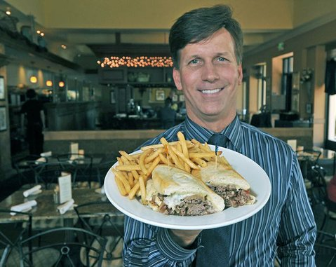 Warren Butler, general manager of Marmalade Cafe, with a Philly Cheesesteak.