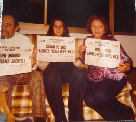 Ralph Morris, Susan Peters (Mastman), and Ruth Morris holding up phony newspaper headlines about coming to Las Vegas.
