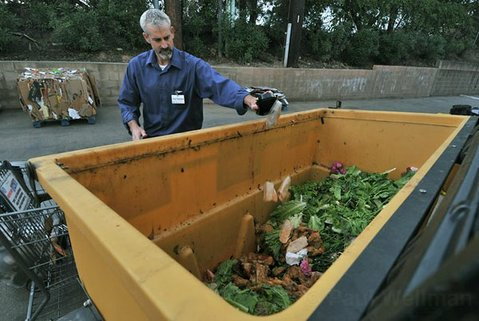 Chris Robertson, assistant store director at the Five Points Center Albertsons, uses new food scrape bins for products that used to go in the dumpster