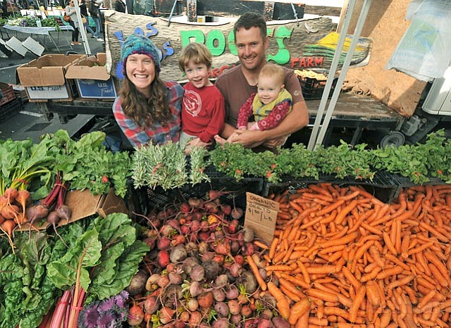 Family-owned Los Olivos Roots Organic Farm (L to R) mom Genevieve Herrick, with children Orin (4 years old), Amelie (15 months), and Jacob Grant at Saturday's Farmers Market.