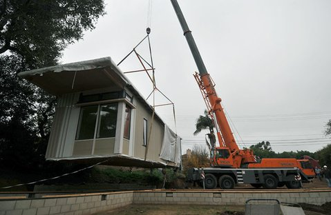 Construction crews crane into place the first of three sections of a modular home