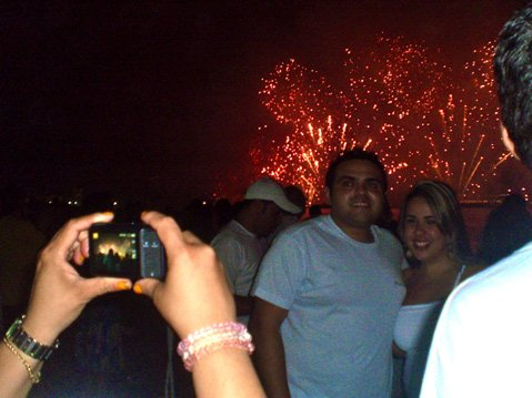 Some Brazilians take their picture in front of the 4km long midnight Réveillon fireworks show.