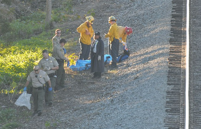 Emergency personnel recover the body of a 16- to 20-year-old male victim who was hit and killed by a passing train just West of the Fairview overpass in Goleta
