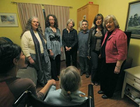 Threshold Choir (L to R) Penelope Salinger, Tessa Flanagan, Marilyn Scott, Hathor Hammett, Luciana Cramer, and Carol Sharpe share a song with a Sarah House resident.