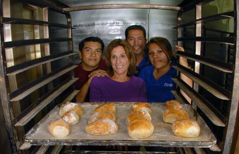 Our Daily Bread staff (from left) Armando, Laurie, Beto, and Armianca, looking through the oven's bread racks.