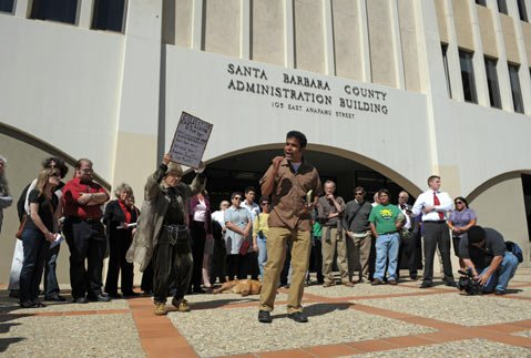 <strong>THE OTHER SIDE:</strong>  Democratic Party Chair Daraka Larimore-Hall (center) inspired a crowd on the steps of the county administration building, gathered Monday morning in support of public employee groups, which have been coming under attack in recent weeks and months.