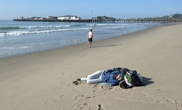 A young couple sleep on the beach during the tsunami advisory.