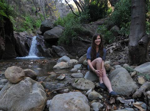 "Zoe Schiffer, here sitting by a creek near her now-rebuilt home, said, ""Growing up in Mission Canyon preserved my innocence …"""