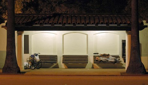 A homeless man sleeps on a bus stop bench on a cold night February 2006.