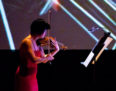 "Jennifer Koh performing in front of Tal Rosner's video projection during the Esa-Pekka Salonen piece ""Lachen verlernt."""