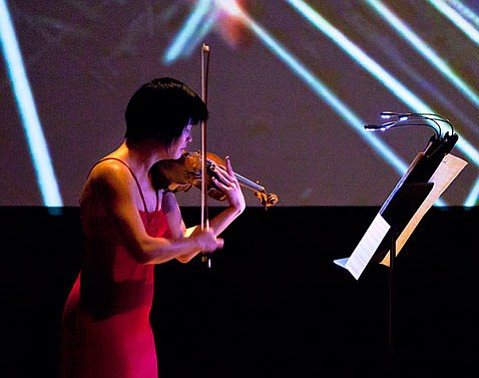 """Jennifer Koh performing in front of Tal Rosner's video projection during the Esa-Pekka Salonen piece """"Lachen verlernt."""""""