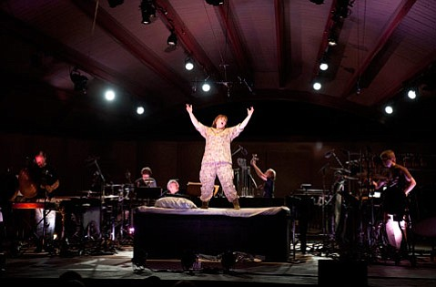 Dawn Upshaw sang George Crumb's <em>The Winds of Destiny</em> from atop an onstage bed in Peter Sellars's dramatic staging. Flanking her are pianist Gilbert Kalish and members of the 