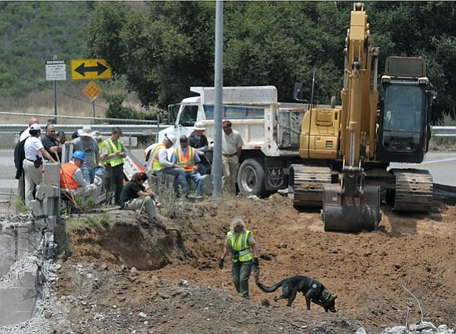 """6/21/11  In the ongoing search for the remains of  Ramona Price, Caltrans heavey machinery operators and cadaver sniffing dogs work with local law enforcement to excavate an """"area of interest"""" in Goleta at the intersection of Calle Real and the recently-demolished Winchester Canyon overpass."""