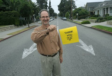 Owen Dell at the intersection of Figueroa and De La Vina, with homemade prototype of traffic flag.