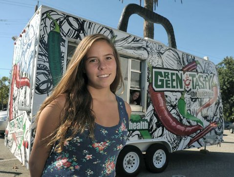 Mariana Duran in front of the Green and Tasty food truck, which is run by Monica Calles (in window).