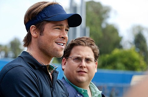 Brad Pitt stars as Oakland A's general manager Billy Beane opposite Jonah Hill as his number-crunching assistant in the based-on-a-true-story baseball movie <em>Moneyball</em>.