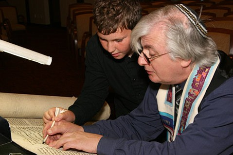 Sofer Neil Yerman works with Max Gaynes, age 10, as they restore a letter in a 200-year-old Czech Torah.