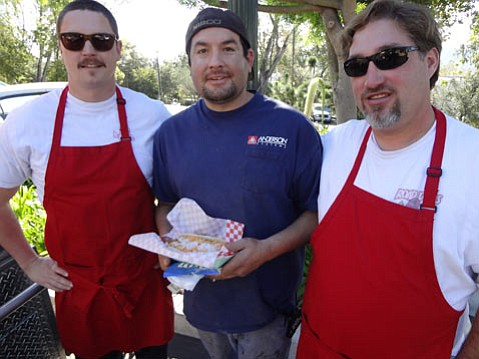 Road Dogs' owner Jared Guthrie (right) and employee Brandon Lee (left), with a satisfied customer.