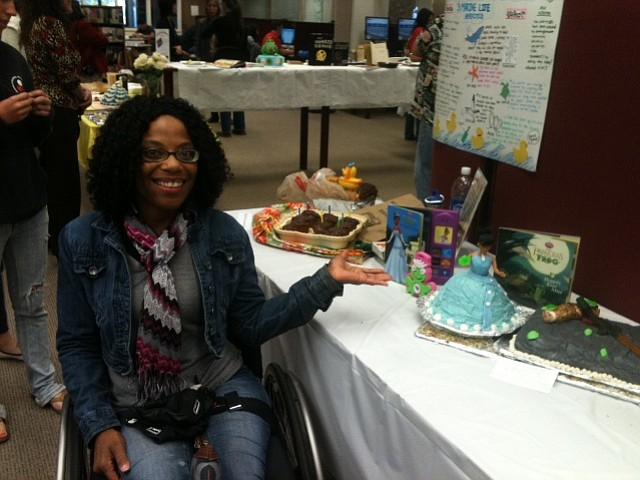 """Stephanie Cissell sits by her """"Princess and the Frog"""" cake"""