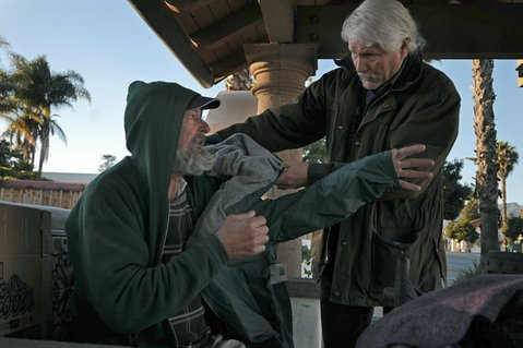 <strong>HELPING HAND:</strong>  After 35 years as a homeless outreach worker, Ken Williams, seen here helping a homeless man named Paul put on a coat, is calling it quits to concentrate on his writing.