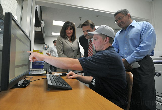 <strong>HARD AT WORK:</strong>  Los Prietos Boys Camp juvenile Skyler W. shows Supervisor Janet Wolf, Sheriff Bill Brown, and Supervisor Salud Carbajal the graphic-design station of the new Los Prietos Business Center in the County Administration Building.