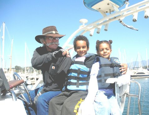 Capt. David Bacon with you young passengers aboard the <em>WaveWalker</em> inside the Santa Barbara Harbor.