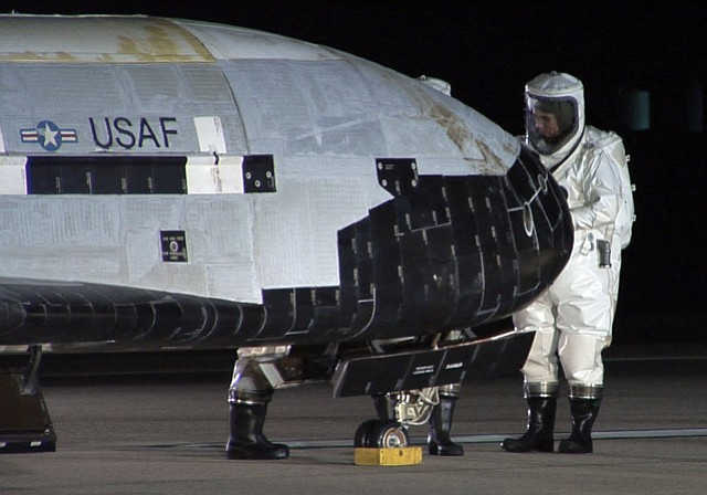 Vandenberg personnel examine an X-37B space plane after it landed at the base in 2010