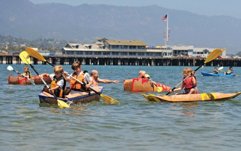 Kayakers try to keep their cardboard creations afloat.