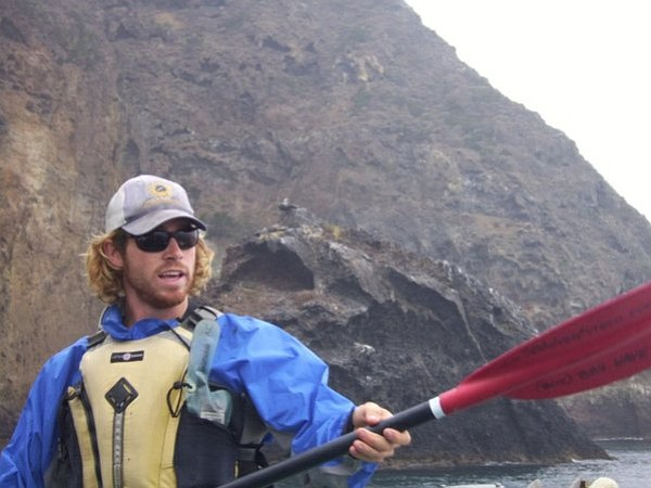 Guide Ryan Boutcher demonstrates how to use the paddle with Quail Rock in the background