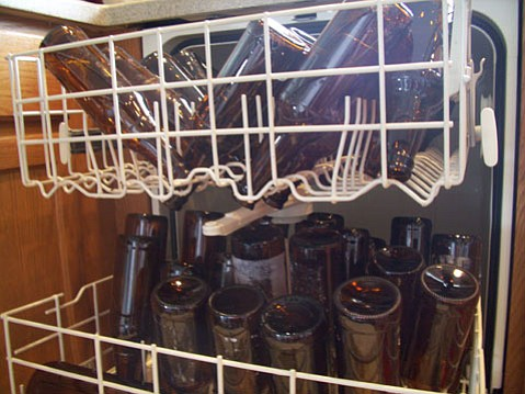 A dishwasher full of bottles to be used.