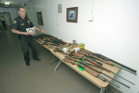 Lt. Paul McCaffrey displays 18 stolen guns that were found in the trunk of Eric Ross's car