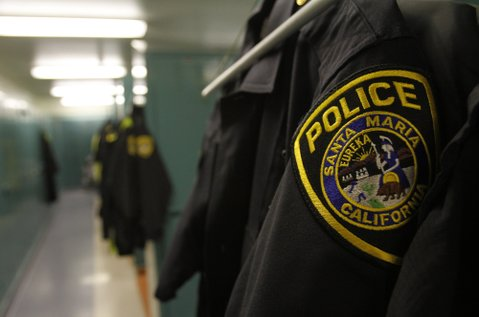Santa Maria Police officers' jackets and gear line the locker room