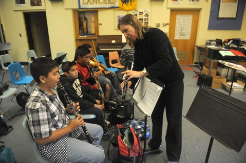 Nancy Mathison helps Salvador Valencia in La Cumbre Junior High's music class
