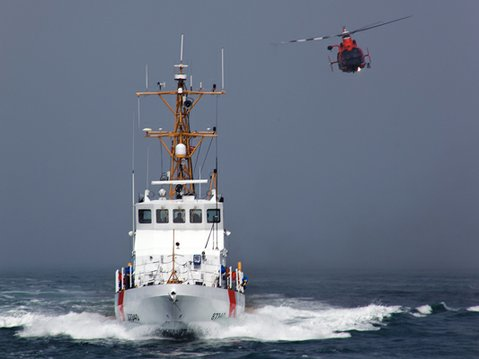A rescue helicopter flies alongside the Coast Guard Cutter Halibut. (August 29, 2011)
