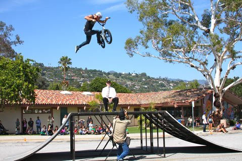Paul Wellman photographs Kris Fox, one of three Team Soil Riders to visit Santa Barbara High School on Bike to School Day, jumping over SBHS Assistant Principal David Hodge (May 9, 2012)