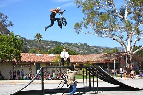 Paul Wellman photographs Kris Fox, one of three Team Soil Riders to visit Santa Barbara High School on Bike to School Day, jumping over SBHS Assistant Principal David Hodge (May 9, 2012)