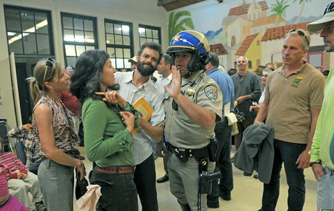 When Jacob Rodriguez (plaid shirt), a skeptic of the pesticide program, started to get unruly at Monday's meeting, California Highway Patrol Officer James Richards stepped in.