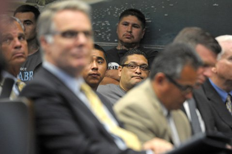 <b>STRADDLING WORLDS:</b>  Raymond Macias stands against the wall of City Council chambers as authorities discuss the potential benefits and repercussions of a proposed gang injunction. In front of him sits J.P. Herrada (in glasses), surrounded by members of Palabra and Santa Barbara law enforcement officials.