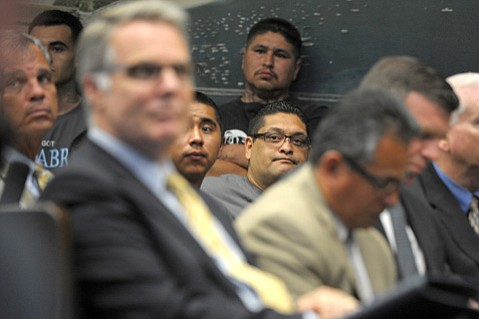 <b>STRADDLING WORLDS:</b>  Raymond Macias stands against the wall of City Council chambers as authorities discuss the potential benefits and repercussions of a proposed gang injunction. In front of him sits J.P. Herrada (in glasses), surrounded by members of Palabra and Santa Barbara law enforcement officials. (May 15, 2013)